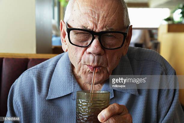 Senior Man Squinting While Drinking Water Through Straw