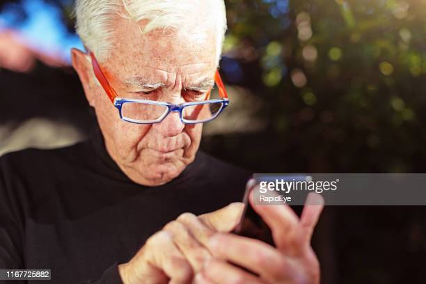 senior man squints at his mobile phone, sending a text - squinting stock photos and pictures