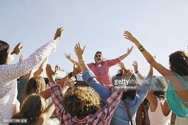 Senior man standing above group of people, arms raised