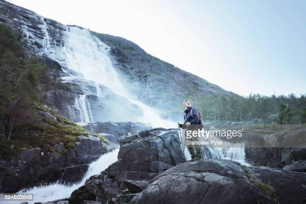 senior man standing against giant waterfall in norway - hordaland county stock pictures, royalty-free photos & images