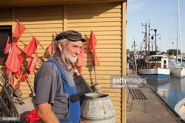 Senior man standing at harbor by boats moored at lake