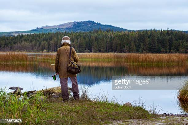 senior man standing beside a scottish loch holding a fly fishing rod - johnfscott stock pictures, royalty-free photos & images