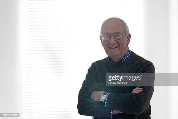 Senior man standing by a window looking happy