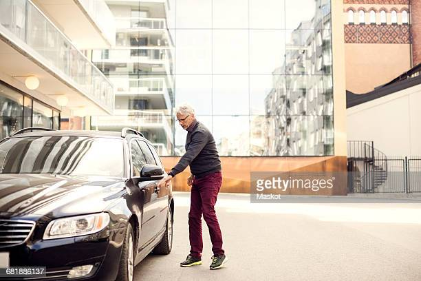 Senior man standing by car against buildings in city