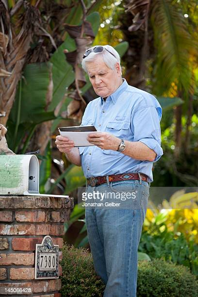 a senior man standing by his mailbox, looking at mail - domestic mailbox stock pictures, royalty-free photos & images