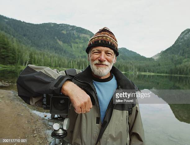 Senior man standing by lake, leaning on camera sitting on tripod