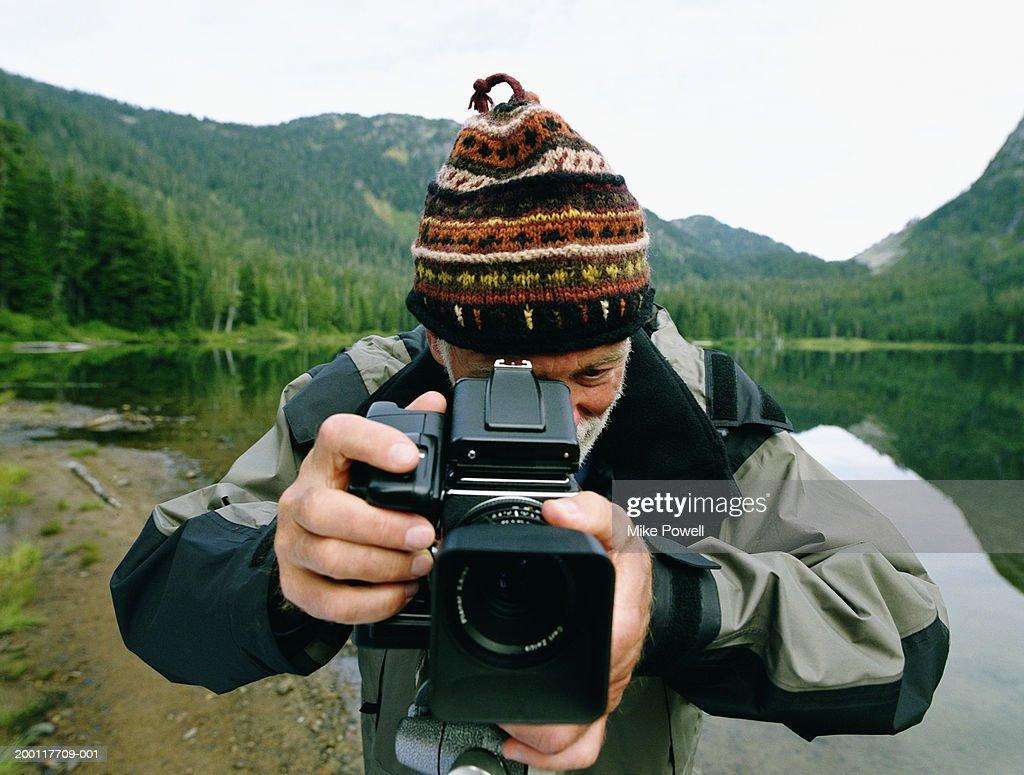 Senior man standing by lake, taking photo with medium format camera : Stock Photo
