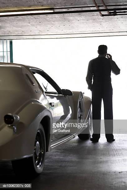 Senior man standing by luxury car in garage, rear view