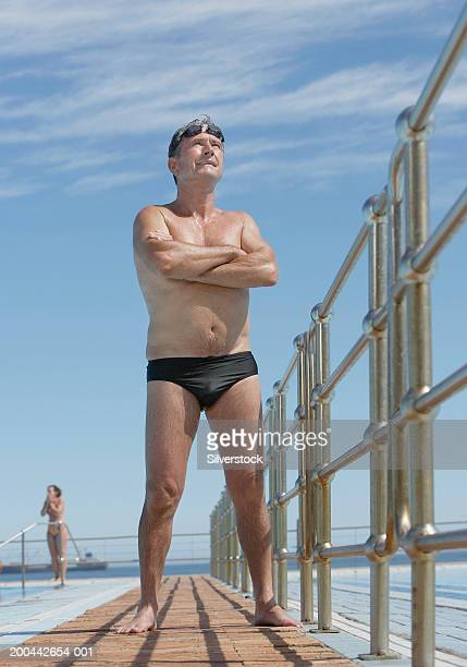 senior man standing by outdoor swimming pool, arms crossed - old man in speedo stock photos and pictures