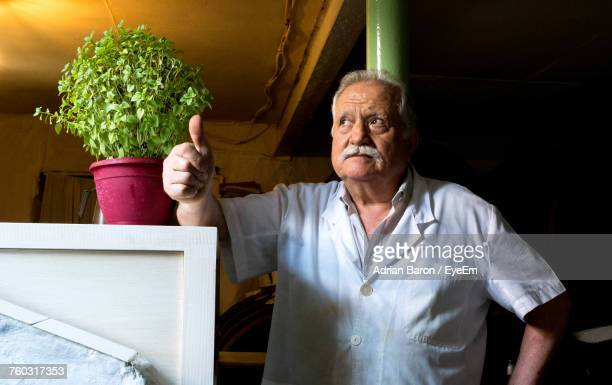 Senior Man Standing By Potted Plant