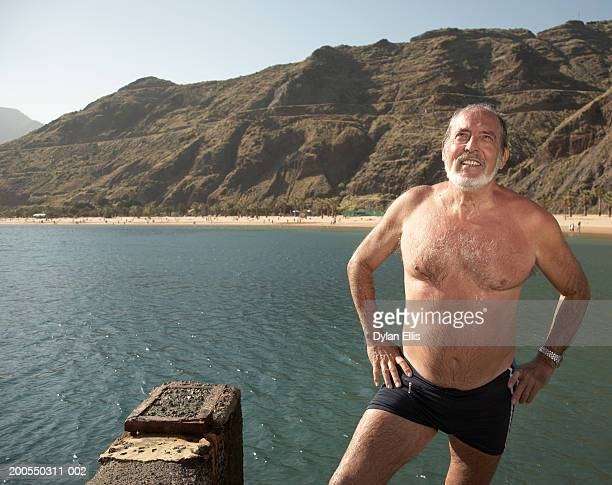 Senior man standing by sea in swimming shorts, hands on hips, smiling