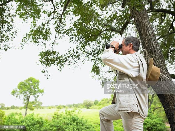 Senior man standing by tree using binoculars, side view