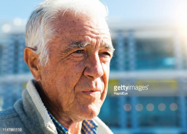 senior man standing in bright sunlight outside building - lentigo stock pictures, royalty-free photos & images