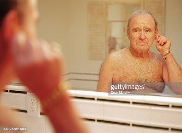 Senior man standing in front of bathroom mirror, cleaning ears