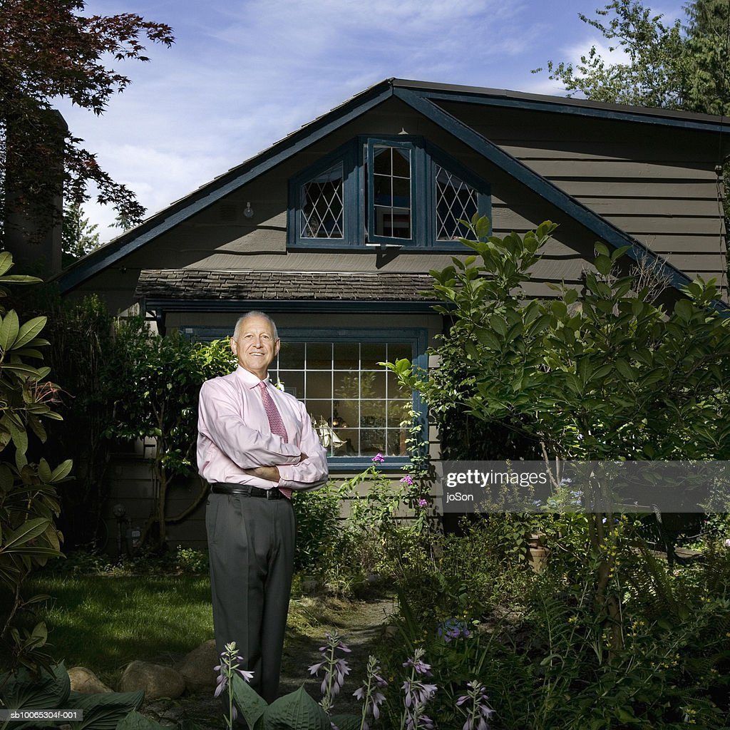 Senior man standing in front of cottage, portrait : Foto stock