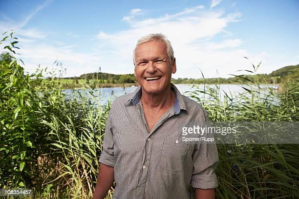 Senior man standing in front of lake