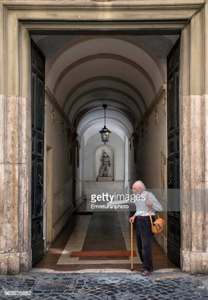 senior man standing in front of the door of a residential building. - emreturanphoto stock pictures, royalty-free photos & images
