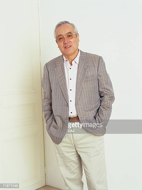 Senior man standing in front of white door with hands in his pocket, looking at camera, Smiling, Front View