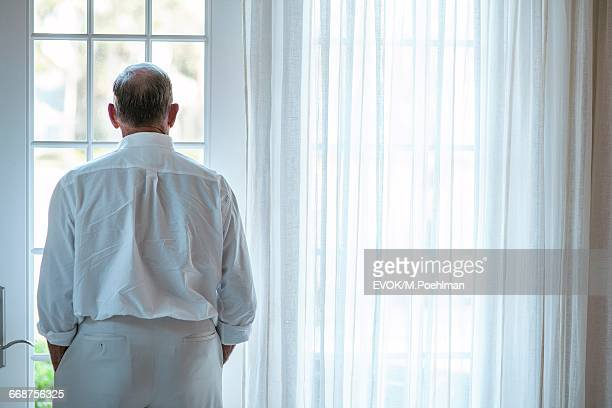 Senior man standing in front of window