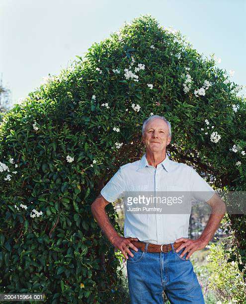 senior man standing in garden with hands on hips, smiling, portrait - hand on hip stock pictures, royalty-free photos & images