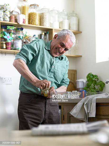Senior man standing in kitchen trying to open jar (focus on man)