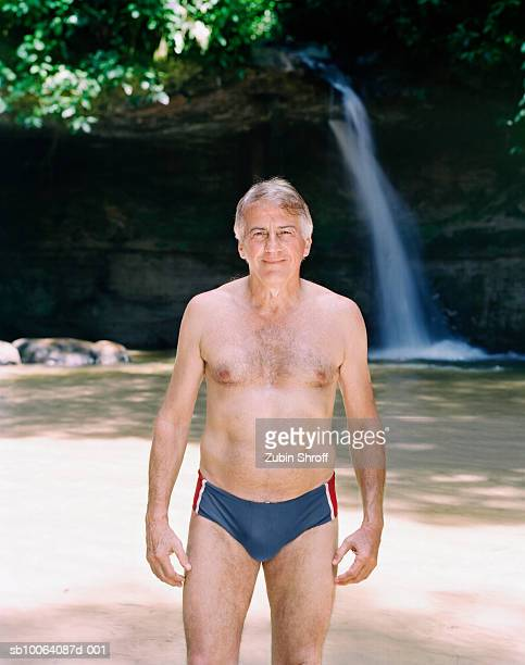 senior man standing in pond, waterfall in background, smiling, portrait - male torso stock photos and pictures