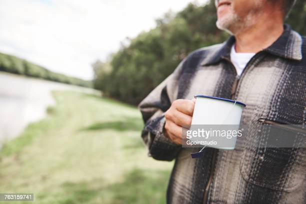 Senior man standing in rural setting, holding tin cup, mid section