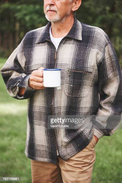 Senior man standing in rural setting, holding tin cup