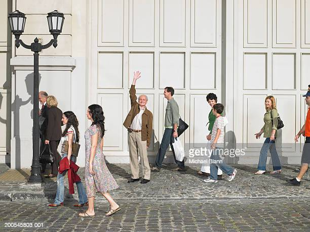 senior man standing in street with hand raised, portrait - moving past stock photos and pictures