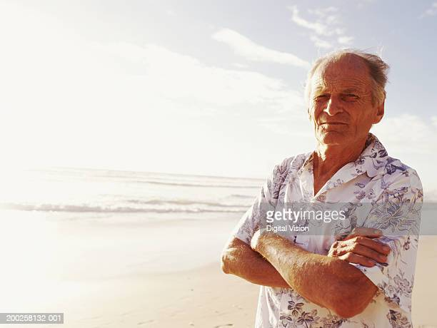 Senior man standing on beach, arms folded, portrait