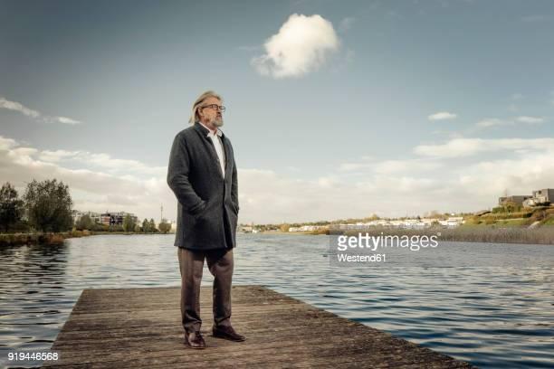 senior man standing on jetty at a lake - coat stock-fotos und bilder