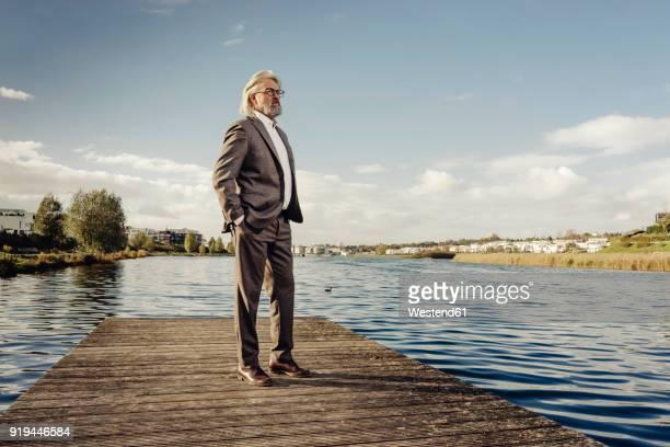 Senior man standing on jetty at a lake