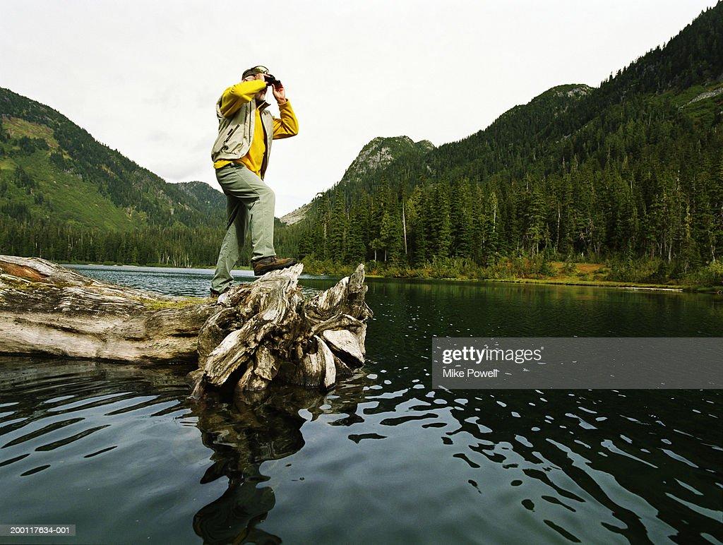 Senior man standing on log floating in lake, looking though binoculars : Stock Photo