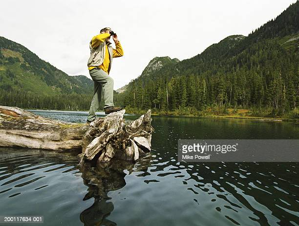 Senior man standing on log floating in lake, looking though binoculars