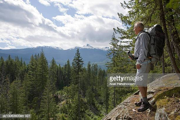 Senior man standing on mountain top, looking at view, carrying backpack