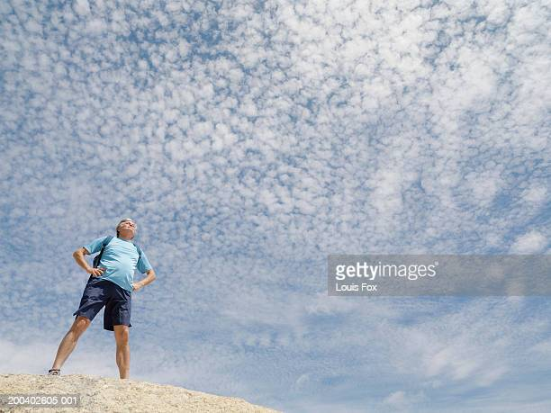 senior man standing on rock outdoors, low angle view - arms akimbo stock pictures, royalty-free photos & images