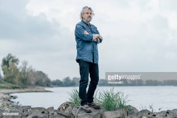 senior man standing on stones looking at rhine river - 65 69 jahre stock-fotos und bilder