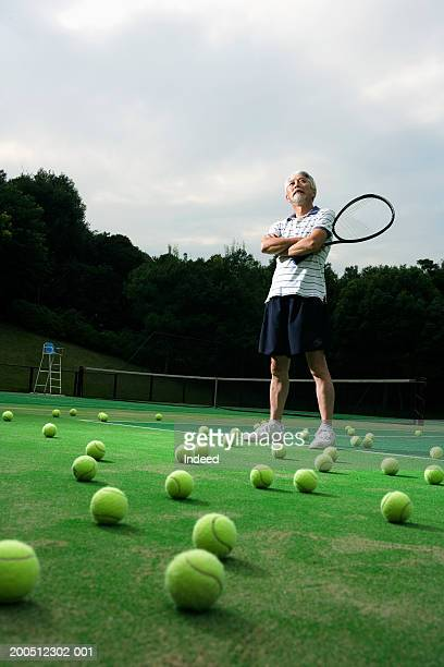 Senior man standing on tennis court, holding racquet, arms folded