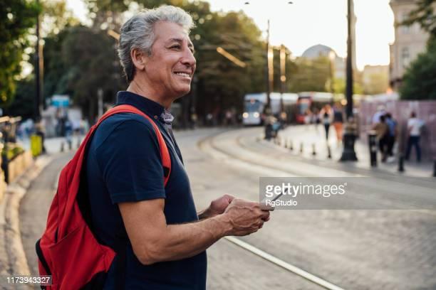 senior man staande op de straat - mobile stockfoto's en -beelden