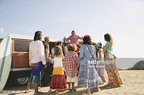 Senior man standing on van above group of people outdoors
