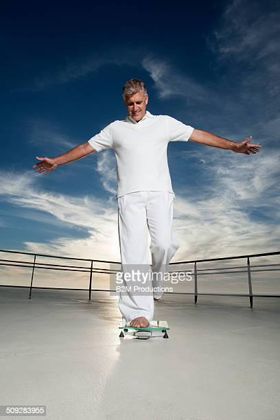 Senior Man Standing On Weighing Scale