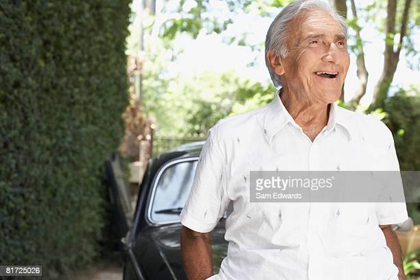 老人男性屋外に立って微笑むお車