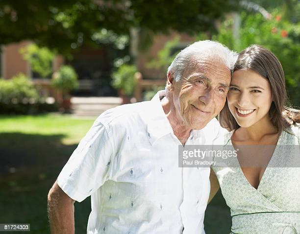 senior hombre de pie al aire libre con brazo alrededor de mujer sonriendo - pareja hombre mayor y mujer joven fotografías e imágenes de stock