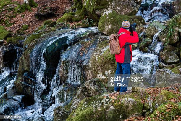 senior man standing to take a photograph of a frozen waterfall using a dslr - johnfscott stock pictures, royalty-free photos & images