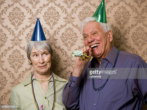 a senior man standing with a senior woman and blowing a party favor - inconvenience stock pictures, royalty-free photos & images