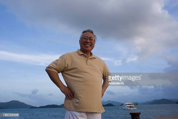 senior man standing with arms akimbo and smiling at the seaside - arms akimbo stock photos and pictures