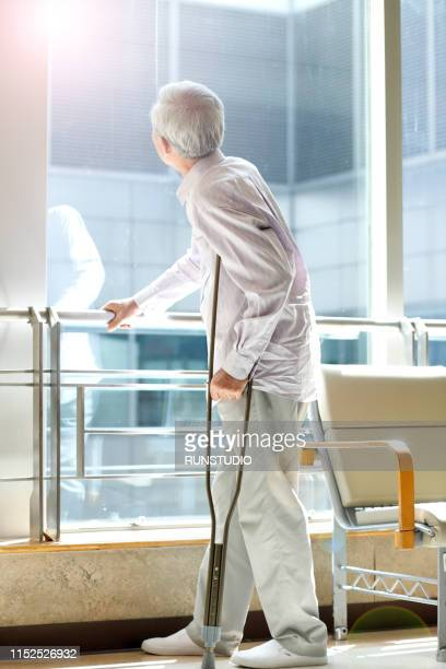 senior man standing with crutches by window - 骨折 ストックフォトと画像