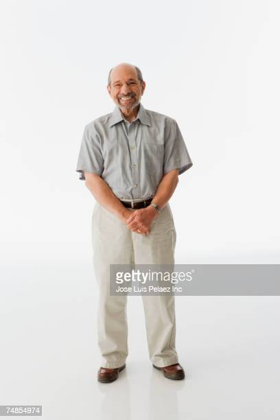 senior man standing with hands clasped - 60 69 jaar stockfoto's en -beelden