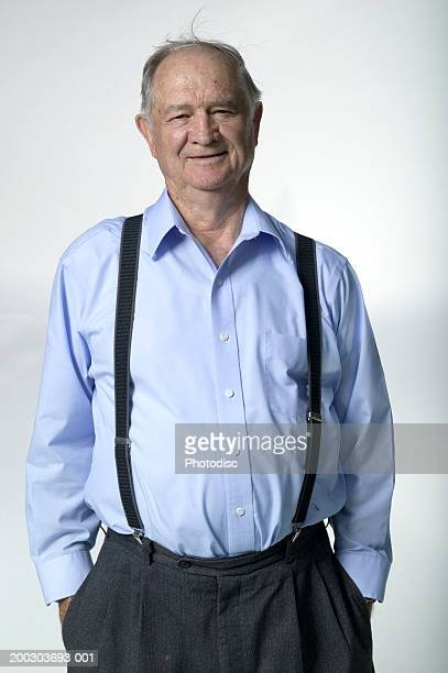 Senior man standing with hands in pockets, smiling, portrait