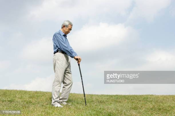 senior man standing with walking cane on field - 杖 ストックフォトと画像